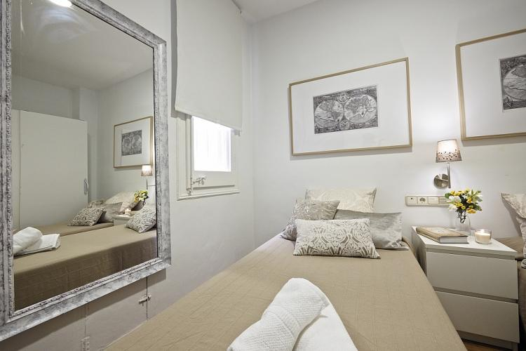 This amazing bedroom with 2 single beds, features a beautiful antique mirror, clean décor and plenty of storage