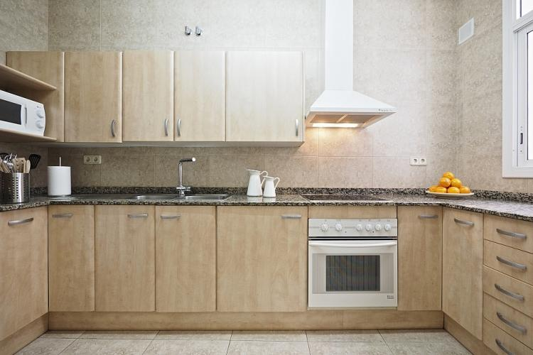 The fully equipped kitchen with its beautiful combination of marble floors and wood cabinets