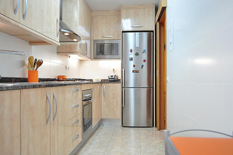 The modern kitchen comes fully equipped with a microwave, oven, stove and refrigerator.