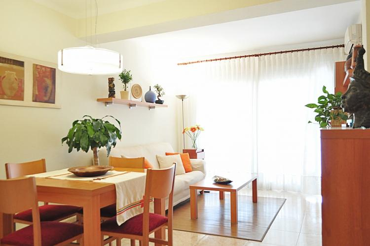 Living room with cozy fold-out sofa and a nice wooden dining table for 4.