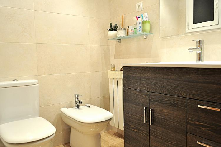 Bright and clean bathroom with toilet and bidet.