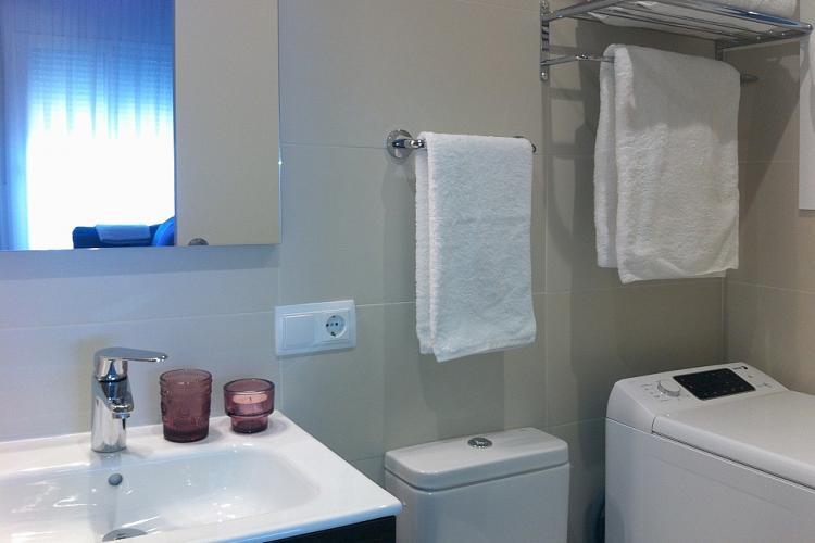 Lavadora-secadora y mueble para guardar cosas del baño.