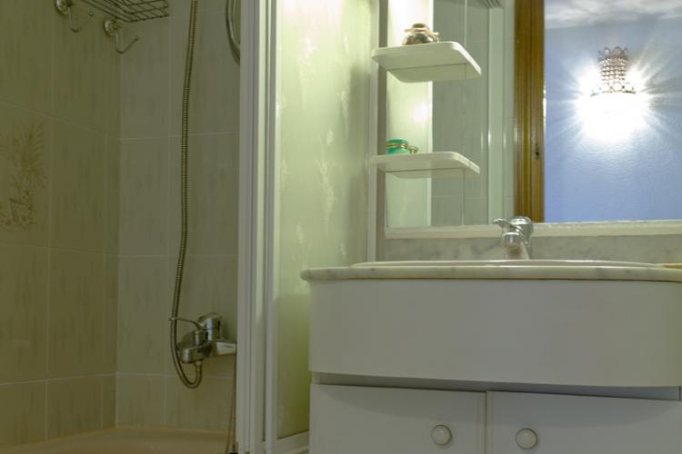 The bright white bathroom is complete with a shower