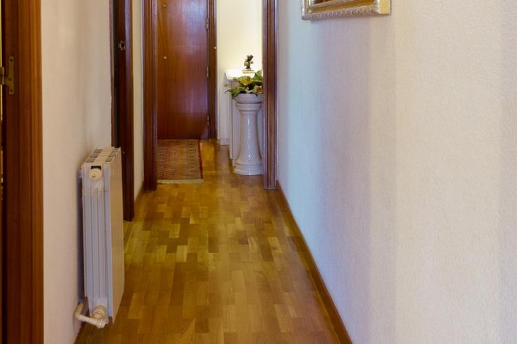 The apartment has a long hallway with a large wall mounted mirror