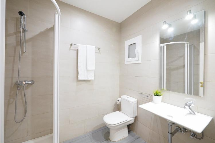 The bathroom has a toilet and shower. Clean towels are provided. Simple design and recently renovated